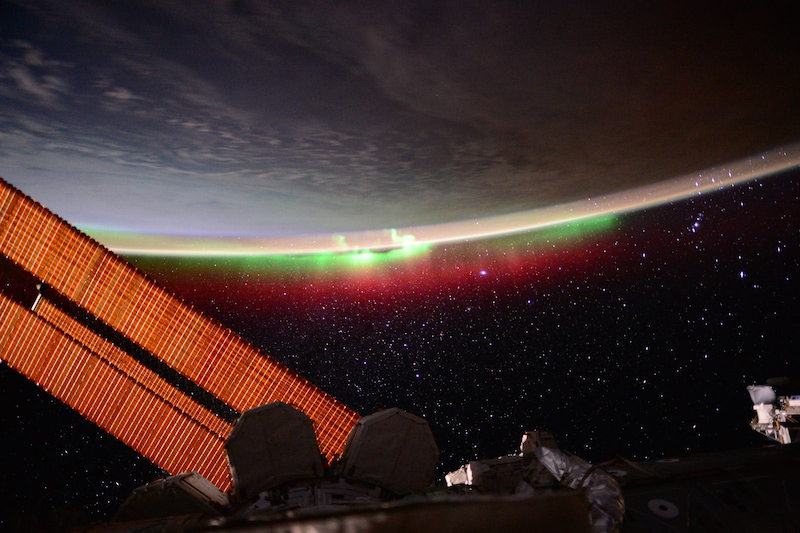 A hint of red and green aurora tint the planet while the International Space Station's solar panels dominate the foreground.