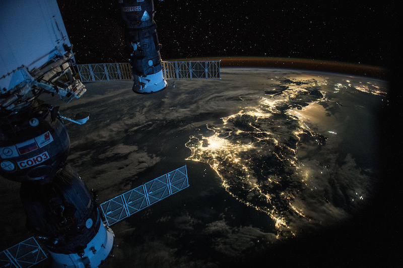 Night over Japan, with the Soyuz spacecraft connected to the Mini Research Module 1 (MRM1) and a Progress cargo tug visible in the foreground