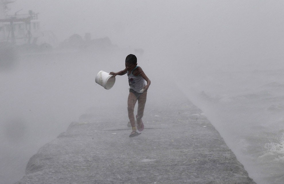 Boy runs as heavy rains and high waves brought by typhoon Linfa