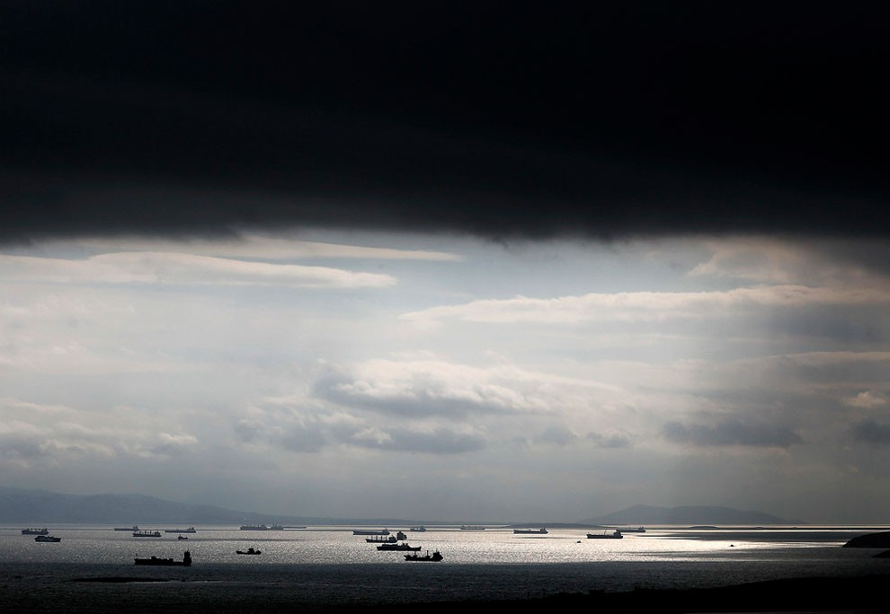 Cargo ships are seen sailing under storm clouds at open sea