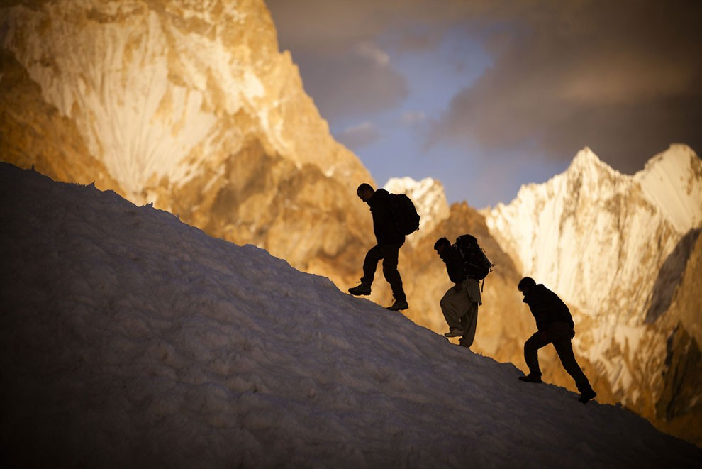 Expedition members meander between crevasses with the Gasherbrum IV massif visible in the background.
