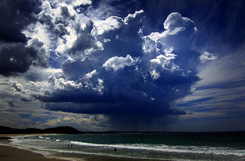 Giant storm cloud can be seen in the sky above swimmers