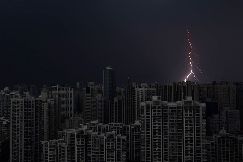 Lightning is seen above buildings during a storm