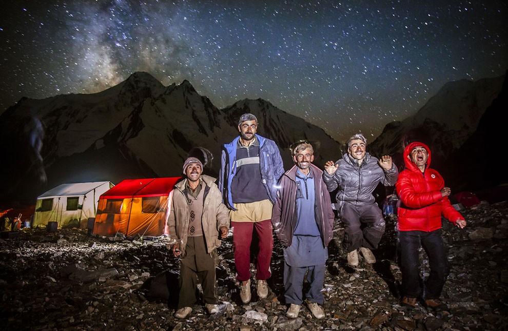 The porters photographed outside at base camp. They sometimes light fires using rubbish from the expeditions.