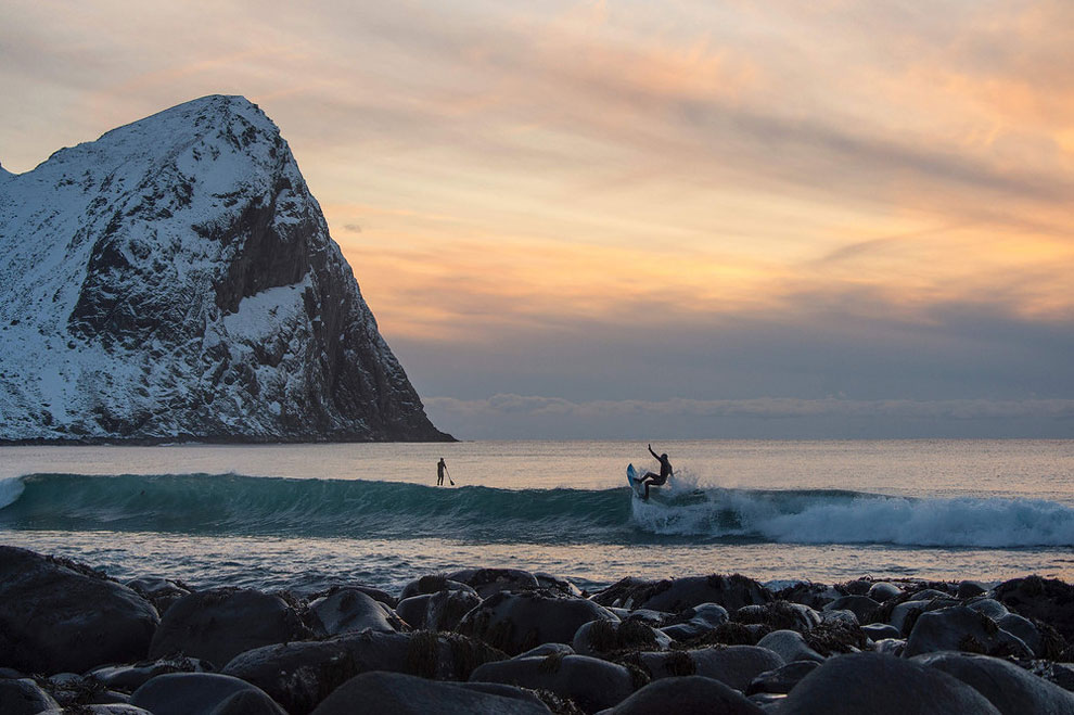 A surfer rides a wave at the snowy beach of Unstad, in Lofoten Island, Arctic Circle, on March 9, 2016.
