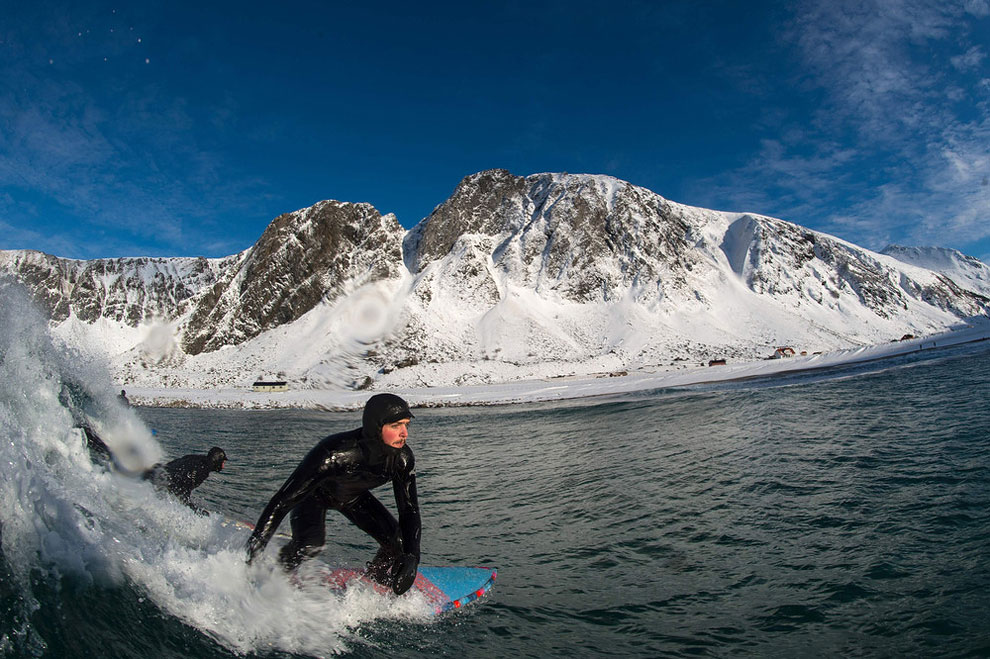 A surfer rides a wave at the snowy beach of Unstad, in Lofoten Island, Arctic Circle, on March 9, 2016
