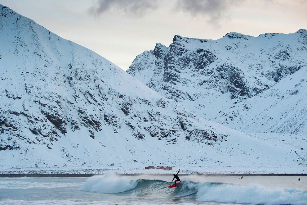 A surfer rides a wave at the snowy beach of Unstad, in Lofoten Island, Arctic Circle, on March 9