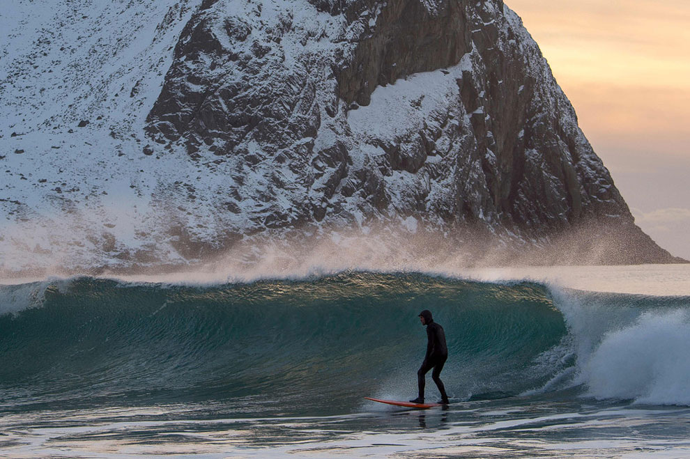 A surfer rides a wave at the snowy beach of Unstad, in Lofoten Island