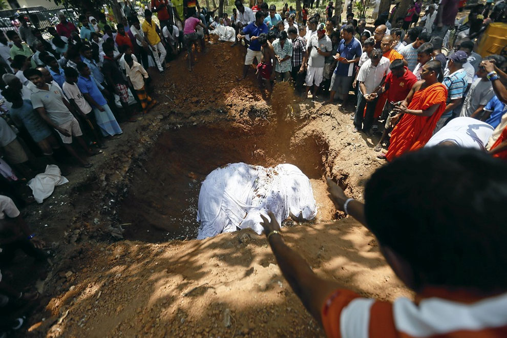 Local villagers prepare to bury the body of elephant Hemantha during a religious ceremony at a Buddhist temple